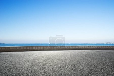 empty rural asphalt road and blue sea in blue sky