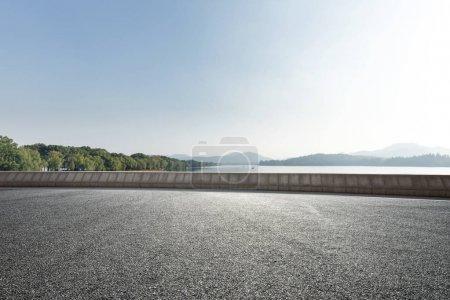 Photo pour Route asphaltée vide près du beau lac dans un ciel bleu ensoleillé - image libre de droit