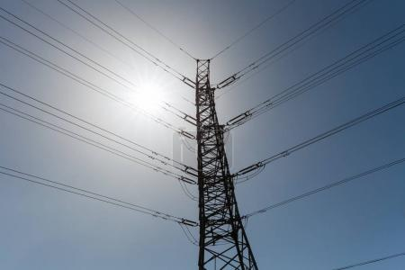 Photo for Electric power pylon silhouette over blue sky - Royalty Free Image