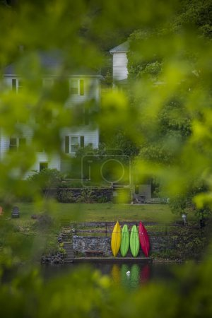 View of stored kayaks across river and through green tree branches