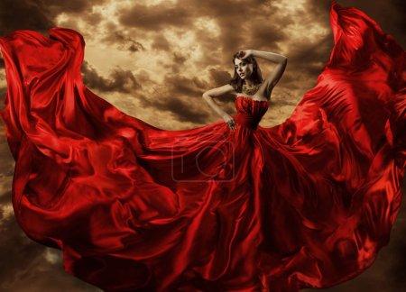 Photo pour Femme dansant en robe rouge, Fashion Model Dance avec le tissu de robe volante, tissu de soie qui coule ondulant sur le vent - image libre de droit