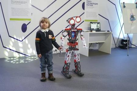 Little boy interacting with smart robot