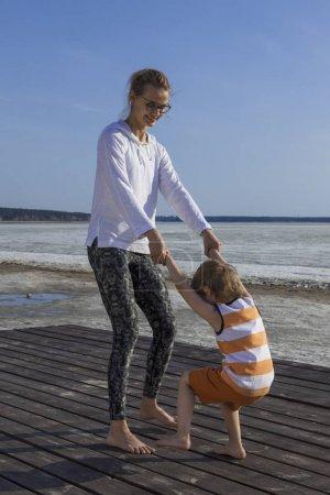 Foto de Joven madre feliz y el niño jugando juntos cogidos de la mano en la playa - Imagen libre de derechos