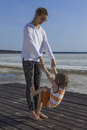 Photo for Happy family. Young mother with her child holding hands and doing exercise on sunny day. Portrait mom and little son on the beach. Positive human emotions, feelings, joy. - Royalty Free Image