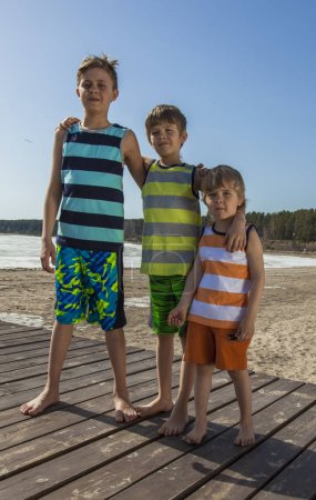Photo for Three happy boys hugging on the beach. Summer vacation. - Royalty Free Image