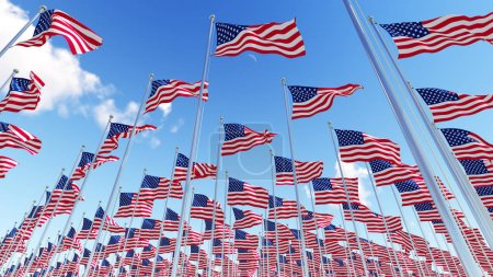 Many flags of USA on flagpoles against blue sky.