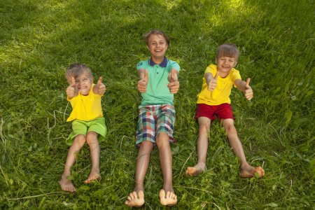 Photo for Three smiling boys sitting on green grass and showing thumbs up. - Royalty Free Image