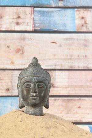 Photo pour Bouddha dans le sable avec fond en bois - image libre de droit