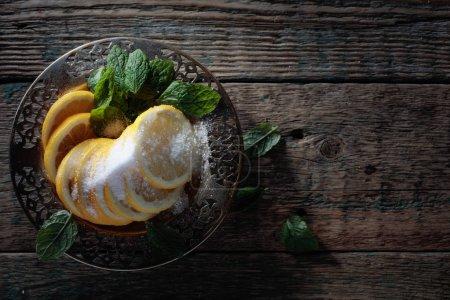 Photo pour Tranches de citron avec sucre et feuilles de menthe sur une table en bois. Vue du dessus, espace de copie . - image libre de droit