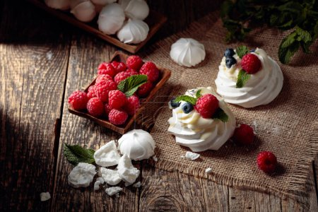 Dessert Pavlova with raspberries, blueberries and mint on a old