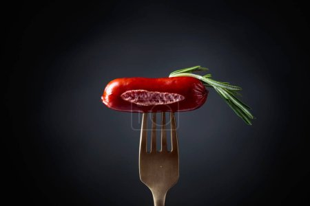 Photo for Grilled sausage with rosemary on a fork. Black background, copy space. - Royalty Free Image