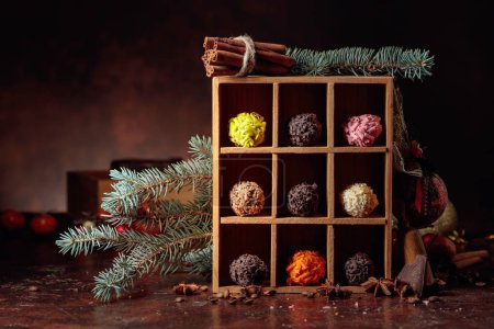 Photo for Chocolate candy in wooden box and Christmas decorations. Broken pieces of chocolate, cinnamon sticks, anise and coffee beans on a brown background. - Royalty Free Image