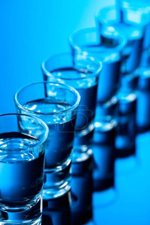 Photo for Glasses of vodka on a black reflective background. Selective focus. - Royalty Free Image