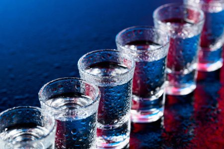Photo for Glasses of vodka on a damp glass table. Selective focus. - Royalty Free Image