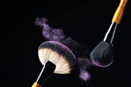 Photo pour Concept de maquillage avec des pinceaux de maquillage professionnels avec fard à paupières violet brillant isolé sur fond noir. Espace de copie . - image libre de droit