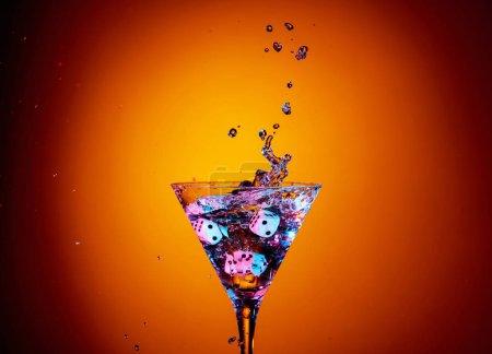 Photo pour Des dés tombent dans un verre de martini. Cocktail coloré en verre avec éclaboussures sur fond orange. Table des matières. - image libre de droit