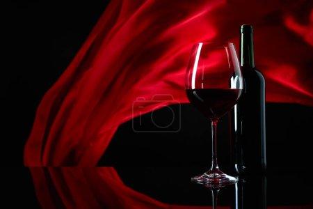 Photo pour Wineglass et bouteille de vin rouge sur un fond réfléchissant noir. Le rideau de satin rouge flotte dans le vent. Espace de copie. - image libre de droit