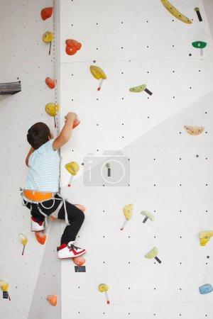 Photo pour Enfant grimpant sur un haut mur - image libre de droit