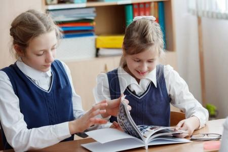 Photo pour Les jeunes élèves dans la salle de classe à l'école look book - image libre de droit