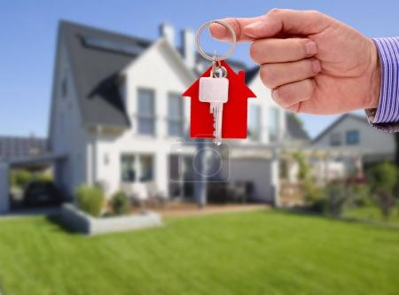 Photo for Key in hand of real estate agent as offer for new residential home - Royalty Free Image