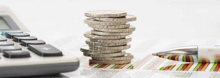 Photo pour Pile de pièces en euros et calculatrice posée sur le tableau des activités financières - image libre de droit