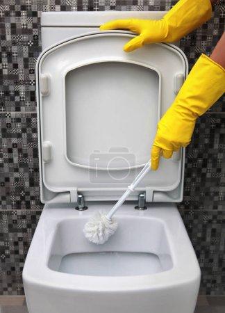 Foto de Limpieza de la taza del inodoro en guantes de goma amarillo - Imagen libre de derechos