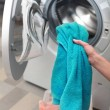Woman loading color clothes from washing machine...