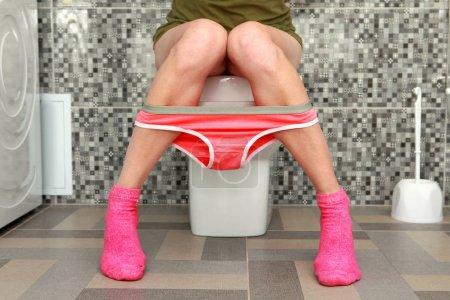 Photo pour Partie de la femme qui est assise sur un bol de toilette - image libre de droit