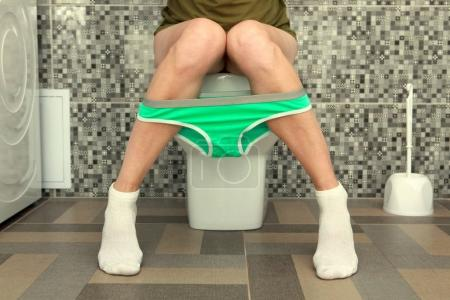 Part of the woman who sits on toilet bowl...