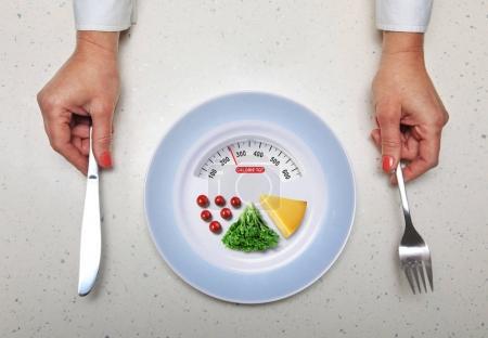 Photo pour Mains avec vaisselle de cuisine et des aliments sains dans la plaque - image libre de droit
