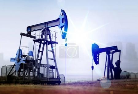 Photo pour Dommages environnementaux causés par le fonctionnement de vieilles pompes à huile en milieu rural contre l'usine - image libre de droit