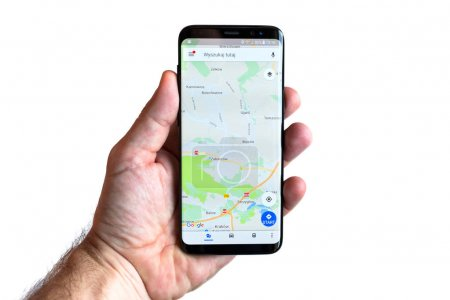 GDANSK, POLAND - NOVEMBER 23, 2017: Brand new black Samsung Galaxy S8 in hand isolated over white background. Google maps navigation on the screen.