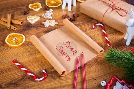 Christmas letter to Santa Claus on wooden table with christmas decorations