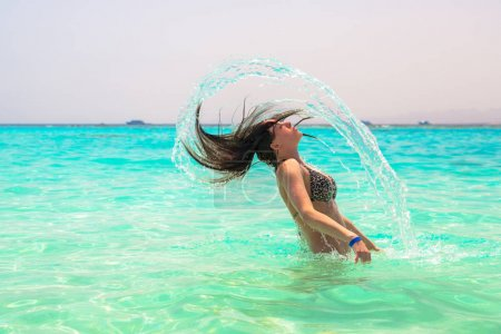 Young woman jumping out of turquoise sea water