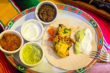 Plate of mexican chicken fajitas with dips