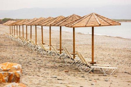 Tropical parasols on empty Maleme beach of Crete, Greece