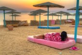 Woman watching sunrise on the beach of Red Sea in Egypt