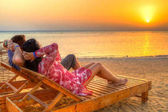 Couple watching sunrise on the beach of Red Sea in Egypt