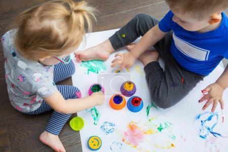 Foto de Hermano y hermana gemelos aprenden a pintar por las manos - Imagen libre de derechos
