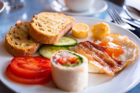 Photo pour Petit déjeuner savoureux dans l'assiette. Œuf frit avec bacon, pain, beurre et salade . - image libre de droit