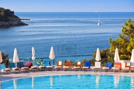 Photo pour Chaises longues et parasols à la piscine par une journée ensoleillée - image libre de droit