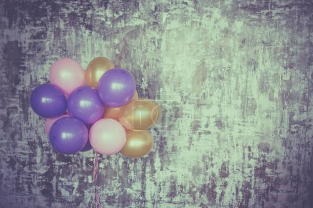 Bright balloons bunch on textured wall