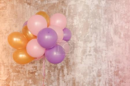 Bright balloons bunch against a textured wall