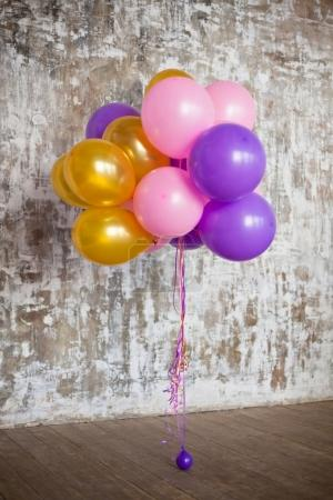 Bright balloons bunch against wall