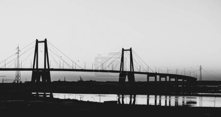 Photo for Black and White silhouette of the large suspension concrete bridge near Figueira da Foz, Portugal - Royalty Free Image