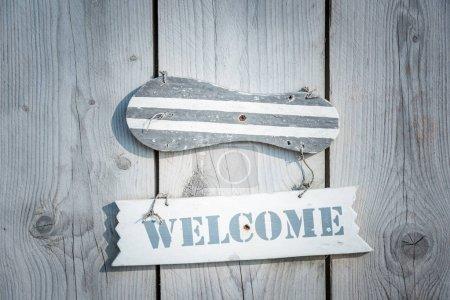 Photo pour Signe de bienvenue en bois dans un style rustique suspendu à la porte de la planche - image libre de droit