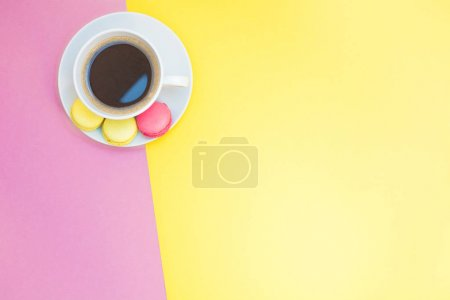 Photo for Creative flat lay photo of coffee cup and macaroons with copy space on pink and yellow background minimal style - Royalty Free Image