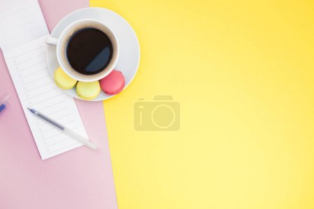 Photo for Creative flat lay photo of coffee cup with macaroons and a notepad with copy space on pink and yellow background minimal style - Royalty Free Image