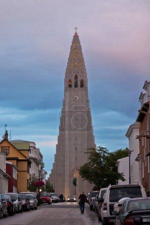 Photo pour Islande, Reykjavik - 21 août 2012: L'église Hallgrimskirkja vu de la rue Skolavordustiger avec des voitures garées le long de la rue - image libre de droit
