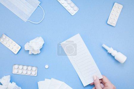 Photo pour Concept créatif plat de l'allergie printanière saisonnière avec serviettes, pilules, masque facial, gouttes dans une bouteille et une main féminine avec espace de copie arrière-plan style minimal, modèle pour le texte - image libre de droit